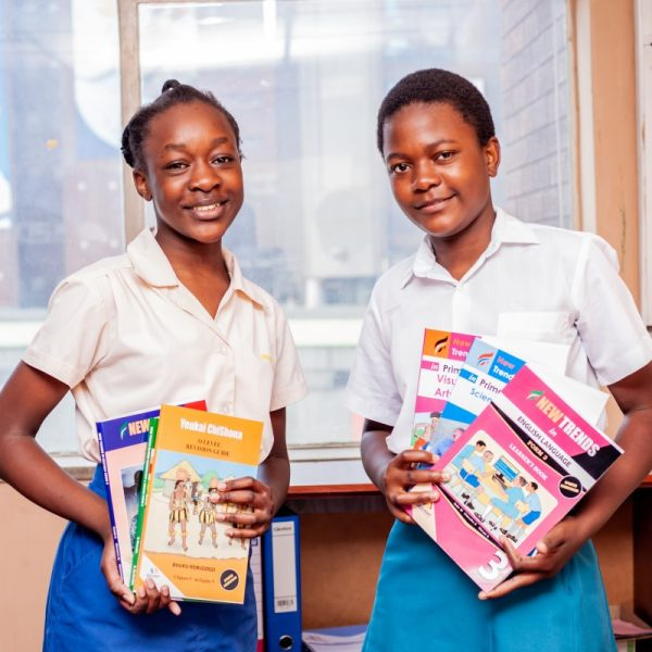 two school girls smiling with edulight books